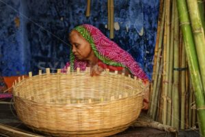 Indian woman in traditional clothes making a basket, Jodhpur, India - GlobePhotos