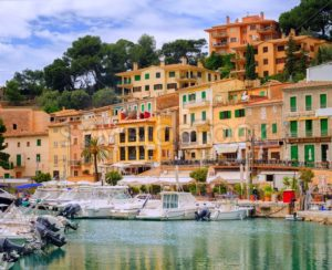 Motor boats and traditional houses in Puerto Soller, Mallorca, Spain - GlobePhotos