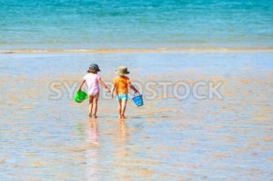Two children playing on a sand beach at sea - GlobePhotos - royalty free stock images