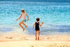 Two kids jumping in the sea waves on a sand beach - GlobePhotos - royalty free stock images