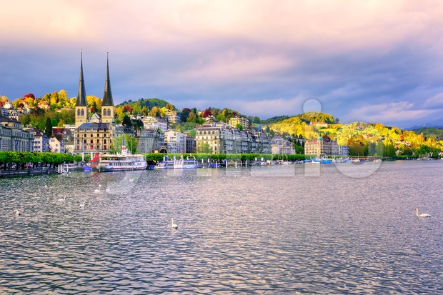 Skyline of Lucerne town with towers of St. Leodegar church and luxury hotels on Lake Lucerne, Switzerland, on sunset