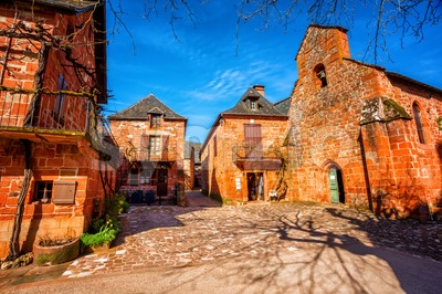 Collonges-la-Rouge, red brick chruch and houses of the Old Town, France Stock Photo