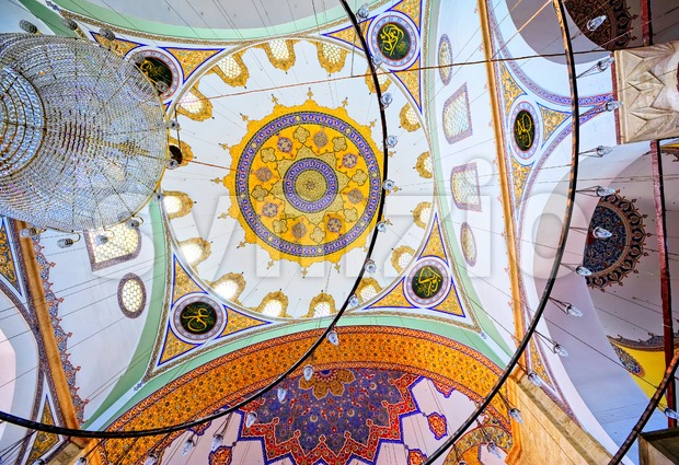 Chandelier and colorful decorated ceiling in the interior of a turkish mosque