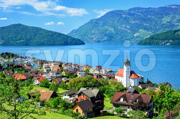 Little swiss town with white gothic church on the shore of Lake Lucerne, Alps mountains, Switzerland