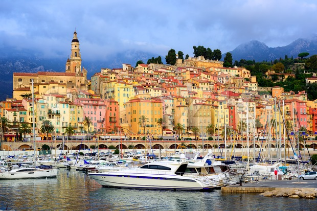 Yachts and boats in the harbour of Menton, in front of colorful medieval old town and Alps Mountains, French Riviera, ...