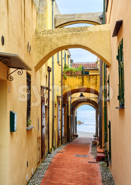 Narrow street leading to the Mediterranean Sea in old town Varigotti, Liguria, Italy Stock Photo