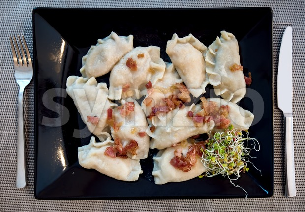 Polish Pierogi stuffed dumplings served in traditional restaurant on a black plate and decorated with ham and green sprouts