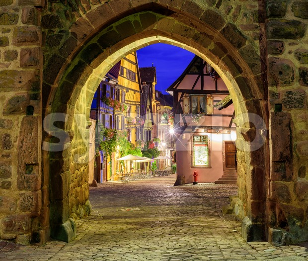 View of Riquewihr, Alsace, France, through city wall gate at night Stock Photo
