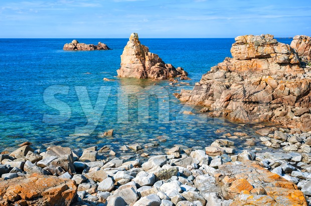 Rocks rising from water at stony beach on Pink Granite Coast, Brittany, France