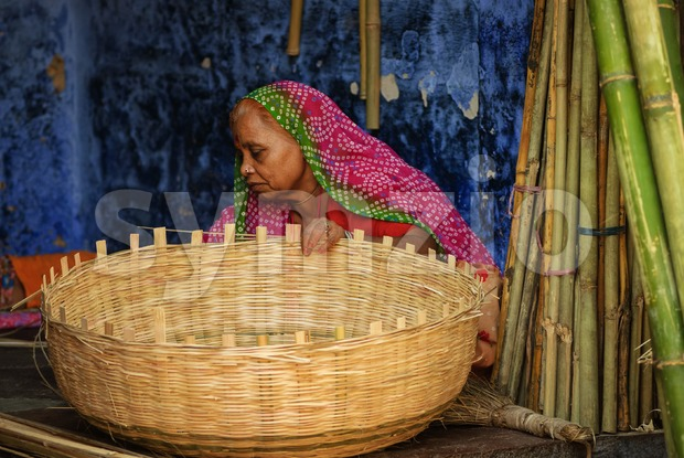 Indian woman in traditional clothes making a basket, Jodhpur, India Stock Photo