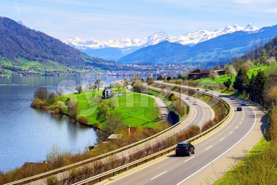 Swiss landscape with a highway, lake and mountains Stock Photo