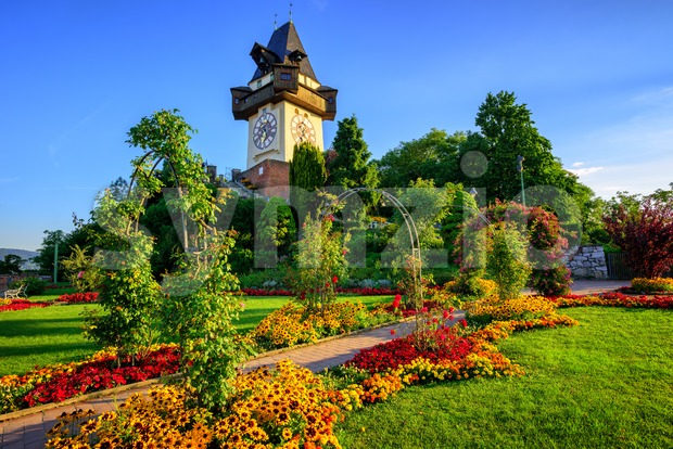 The medieval Clock tower Uhrturm in flower garden on Shlossberg hill, Graz, Austria