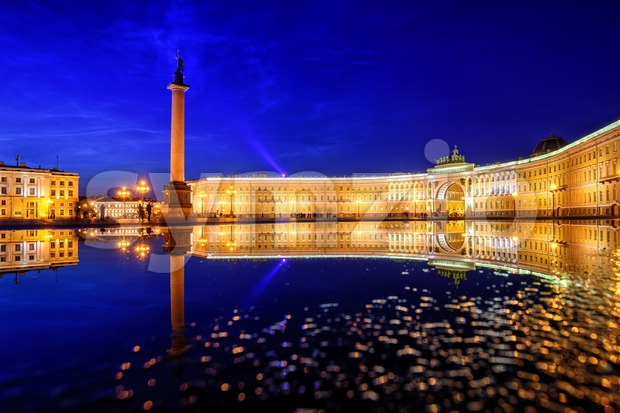 General Staff building and Alexander Column reflecting in rain water on Palace Square in St Petersburg, Russia, on white summer ...