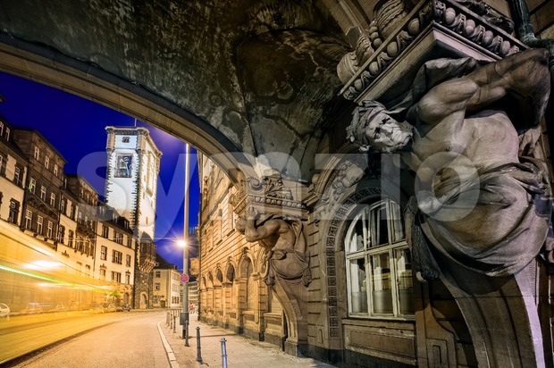Night scene with the moving tram and sculpture figures in the old town of Frankfurt Main, Germany