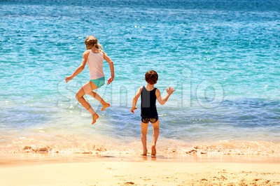 Two kids jumping in the sea waves on a sand beach Stock Photo