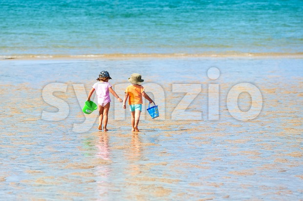 Two kids playing buckets on a sand beach on a warm sunny summer day