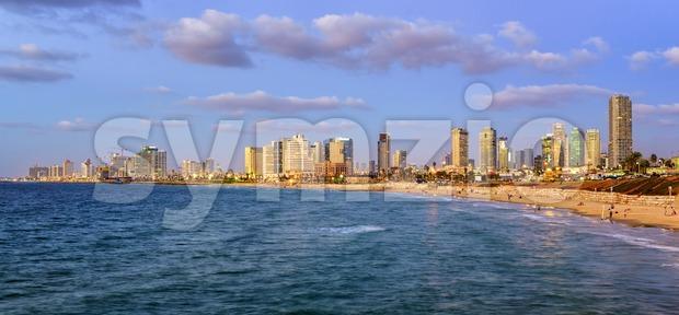 Modern skyline and sand beaches of Tel Aviv city on sunset, Israel