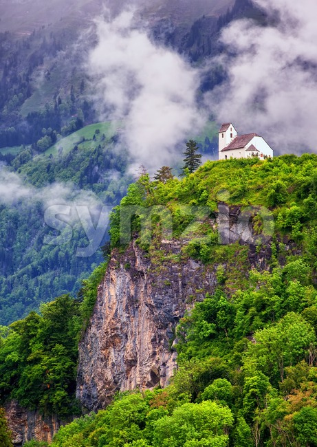Church on a rock in swiss Alps mountains Stock Photo