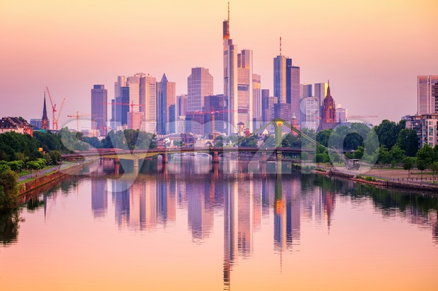 Frankfurt financial district skyscrapers reflecting in Main river, Germany, on sunset