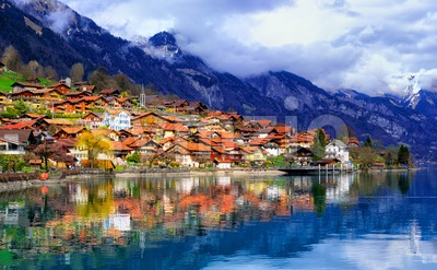 Old town and Alps mountains reflecting in lake, Switzerland Stock Photo