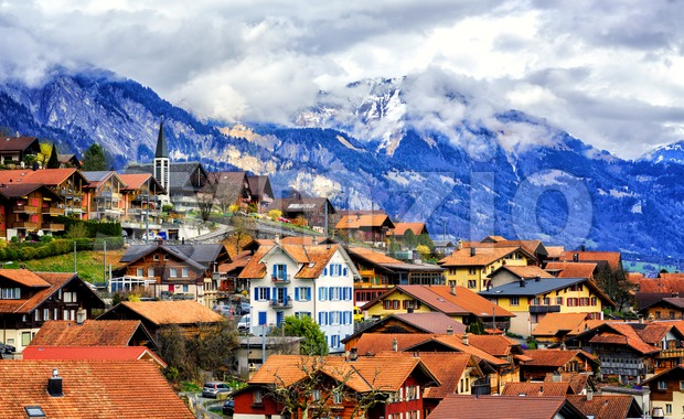 Red tile roofs of the Old Town of Oberried, Brienz, Interlaken and cloudy Alps mountains in background, Switzerland