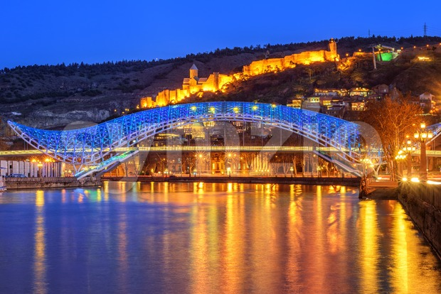 Tbilisi Old Town with the illuminated Europe Bridge over Kura river and Narikala Fortress at evening, Georgia