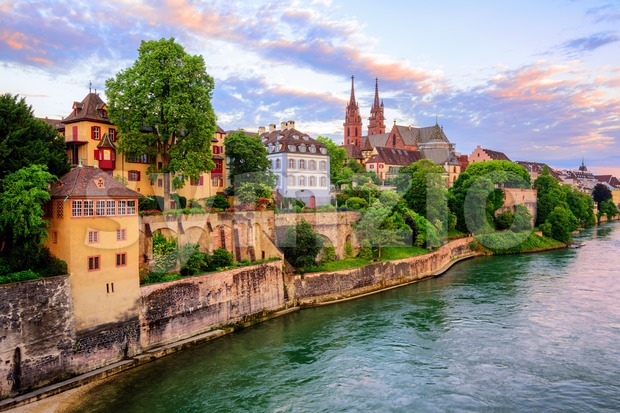 The Old Town of Basel with red stone Munster cathedral and the Rhine river, Switzerland, in dramatic sunset light