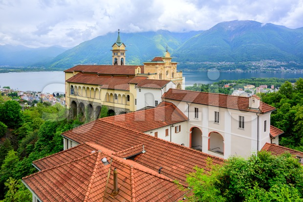 Red tiled roofs of Madonna del Sasso Church over Lago Maggiore lake and swiss Alps mountains, Locarno, Switzerland