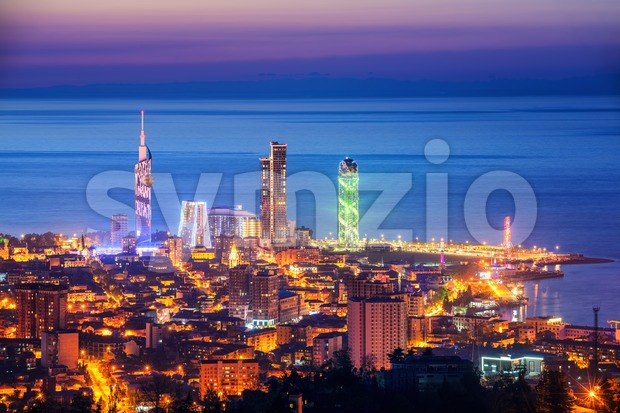 Modern urban center and the Old Town of Batumi city, Georgia, a famous resort town on Black Sea coast, illuminated ...