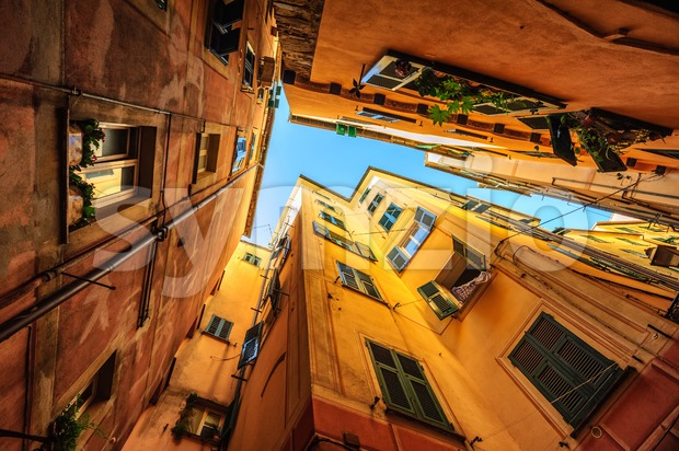 Looking upward a narrow street with traditional yellow houses in Genoa, Italy