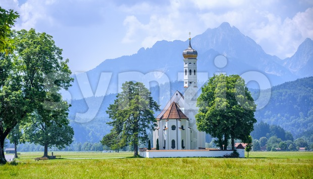Historical St. Coloman white church in Schwangau, Bavaria, Germany, Alps mountains, on a sunny summer day