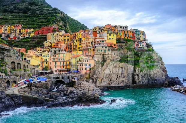 Colorful houses hanging on a rock in the picturesque Manarola Old Town on Mediterranean sea coast, Cinque Terre, Liguria, Italy