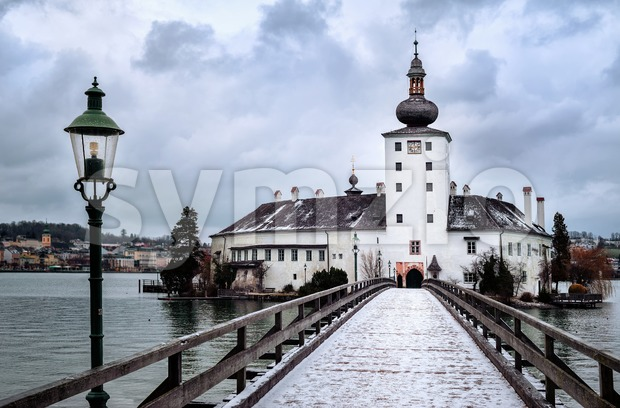 Snow covered wooden bridge leading to a white church on a lake island in Gmunden near Salzburg, Austria