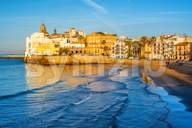 Fine sand beach and historical Old Town in mediterranean resort Sitges near Barcelona, Costa Dorada, Catalonia, Spain, in the early ...