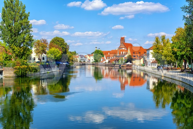 Landshut gothic medieval Old Town, Bavaria, Germany, reflecting in Isar river on a summer day with blue sky and white ...