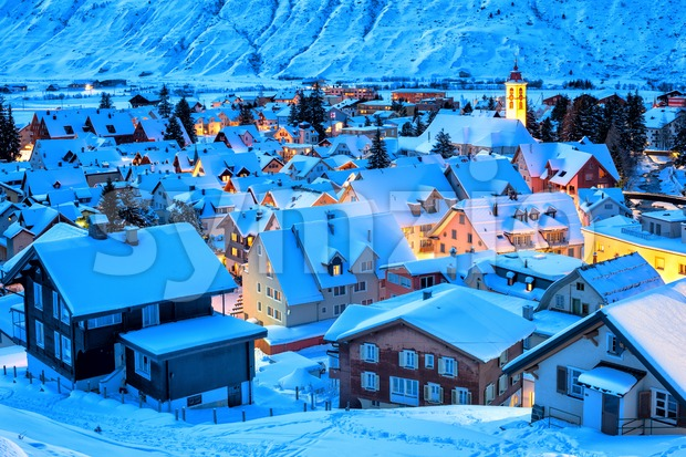 Andermatt village in swiss Alps mountains, snow covered in winter in blue evening light, Uri, Switzerland