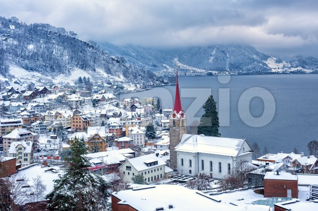 Weggis village on Lake Lucerne, swiss Alps mountains, Switzerland, covered with white snow in winter time