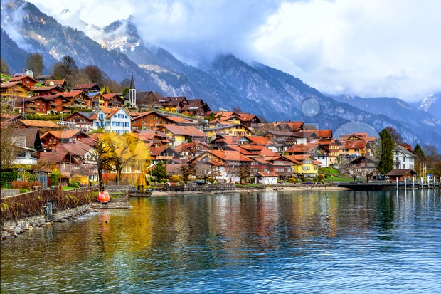 Old town of Oberried, Brienz, Interlaken and misty Alps mountains reflecting in lake, Switzerland