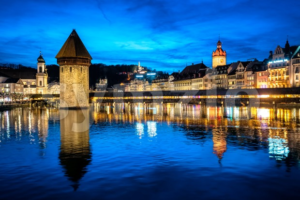 Lucerne, Switzerland, the Old town and Chapel bridge reflecting in river in the late evening blue light