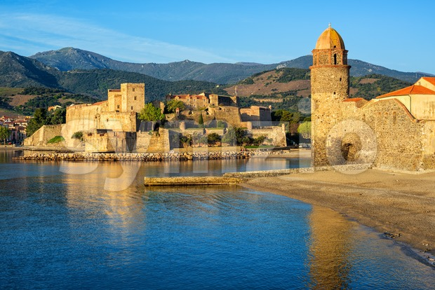 Collioure town, France, view of the medieval Chateau Royal castle and Church tower between Pyrenees mountains and Mediterranean sea