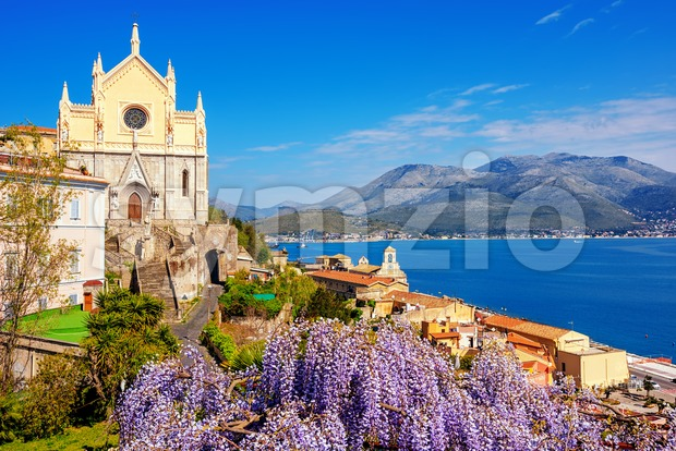 Gaeta, Italy, blooming wisteria flowers and historical churches of St Francis of Assisi and Santissima Annunziata over the blue waters ...