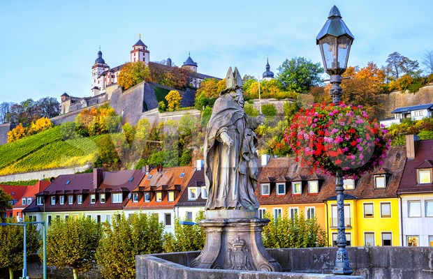 Wurzburg, Bavaria, Germany, view of the Marienberg Fortress from the Old Main Bridge with stone sculpture of religious saint St ...