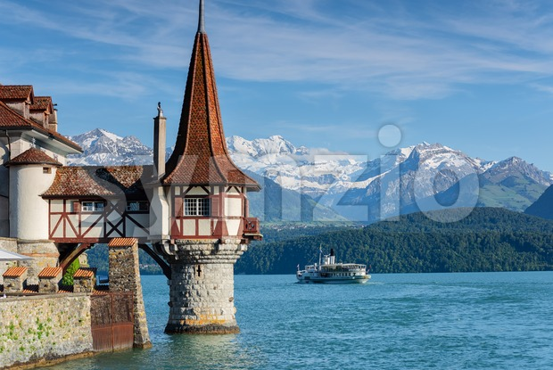 Lake Thun, Switzerland, cruising ship passing between the beautiful Water tower of medieval Oberhofen castle and snow covered Bernese Highland ...