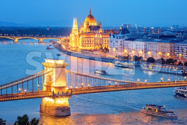 Budapest city, Hungary, view of the Chain bridge over Danube river and Parliament building glowing gold in blue evening light