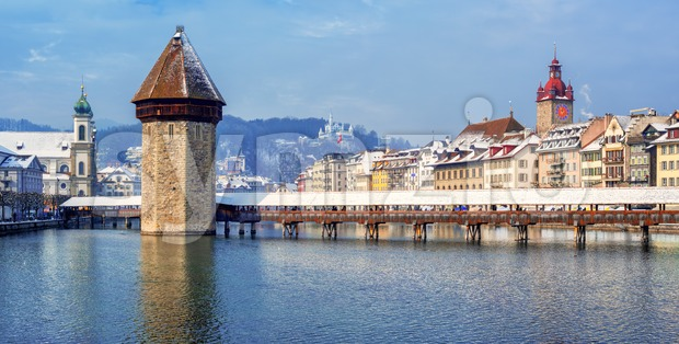 Panoramic view of Lucerne Old town, Switzerland, with wooden Chapel bridge and Reuss river, snow covered on a cold winter ...