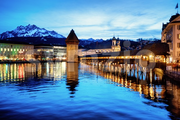 Lucerne, Switzerland, the wooden Chapel bridge, the Old town, Reuss river and Mount Pilatus in blue evening light