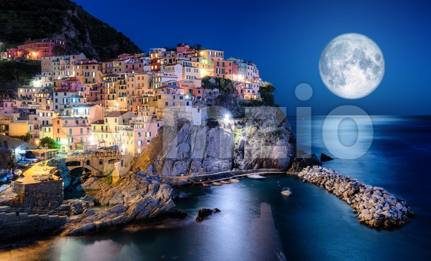 Photo collage of the full moon rising over Manarola village in Cinque Terre, Liguria, Italy at night