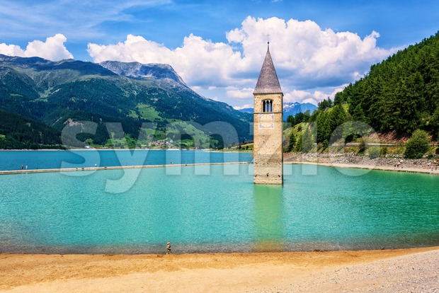 Overflooded Bell tower of the church of Graun, a drawned town, sumberged in the lake Reschen in Alps mountains, South ...