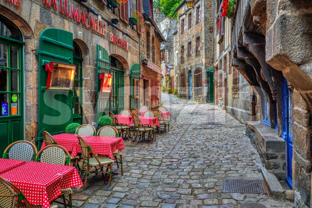 Dinan, France - 10 July 2017: Typical narrow cobbled street with outdoor cafes in the historical Old town of Dinan. ...