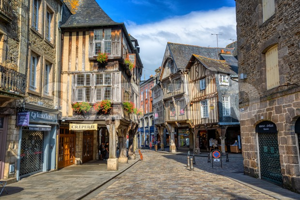 Dinan, France - 10 July 2017: Traditional half-timbered medieval houses on a central street in the historical Old town of ...